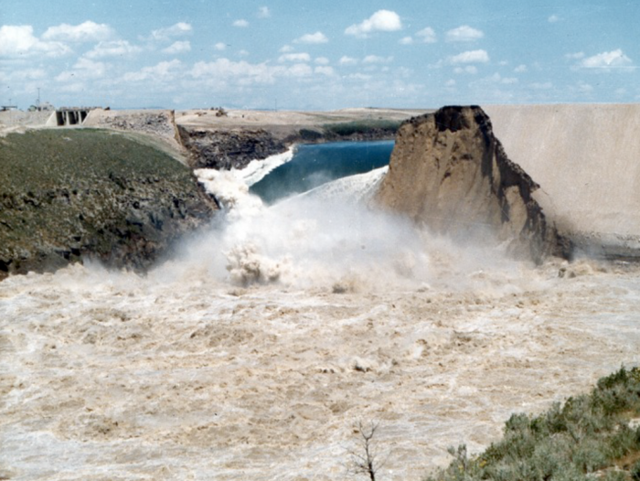 View from downstream of rapid release of the Teton Reservoir after failure during the first filling.  The first filling of the reservoir lacked proper planning and caused water levels to reach design elevations prior to the construction of the auxiliary spillway and outlet works.